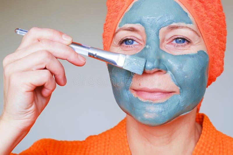 在面孔的化妆面具 美丽的年轻女人接近的画象有毛巾的在有她的头皮肤护理做法 ?? 库存照片