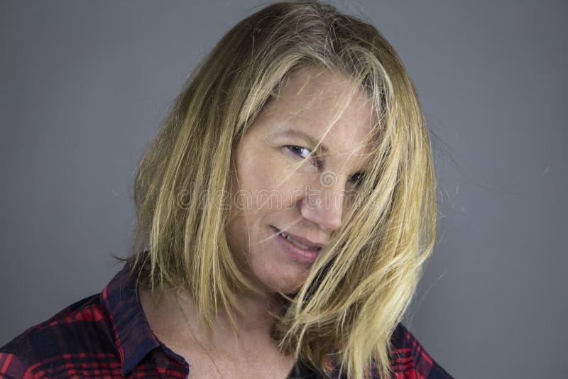 在面孔的白肤金发的女性头发 图库摄影
