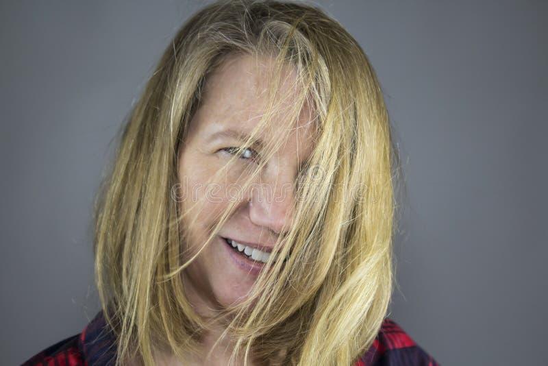 在面孔的白肤金发的女性头发 库存图片
