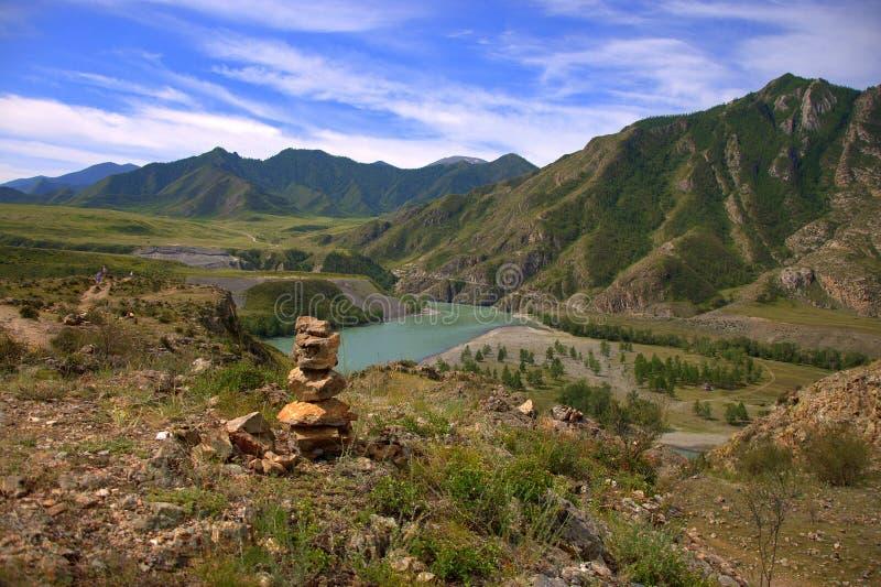 在面对山和河的小山顶部的荐骨的石标 Katun,阿尔泰,西伯利亚,俄罗斯 ?? 库存图片