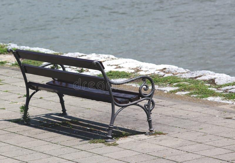 在面对河的江边的长木凳 库存图片
