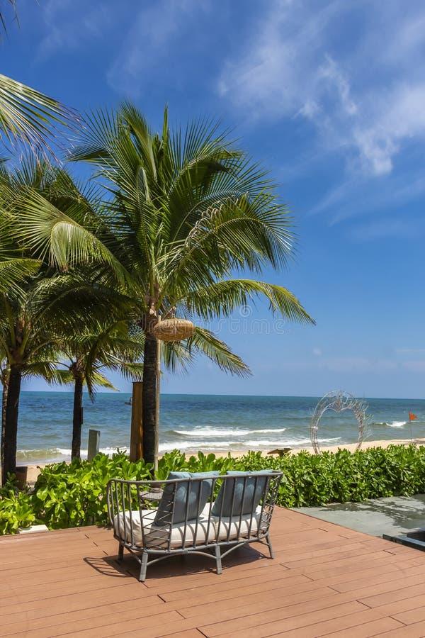 在面对海滩的大阳台的一个室外藤条沙发 库存图片