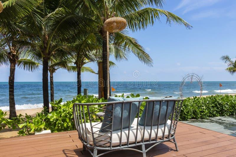 在面对海滩的观察台的户外藤条沙发 库存图片