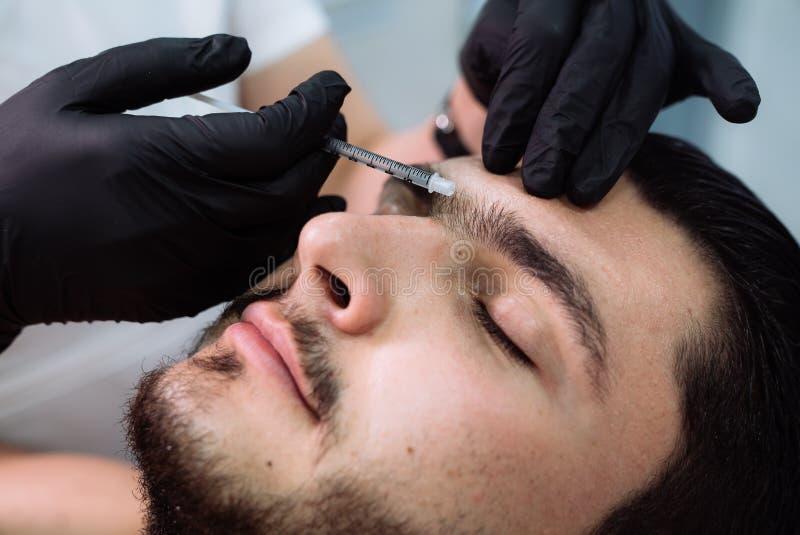 在面部秀丽射入期间,关闭有注射器的男性耐心面孔和美容师` s手 整容术概念 免版税图库摄影