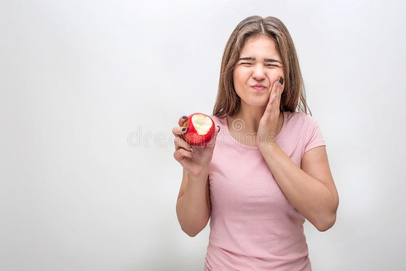 在面颊的不快乐的年轻女人举行手 她有牙痛 模型遭受 她在手中食用苹果 查出在灰色 库存图片