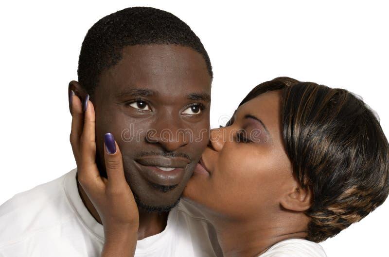 在面颊的非洲夫妇亲吻 库存照片