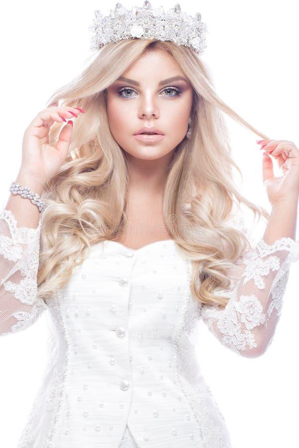 在鞋带婚礼礼服的美好的blondie女孩在她的头的模型与卷毛和冠 秀丽表面 免版税库存图片