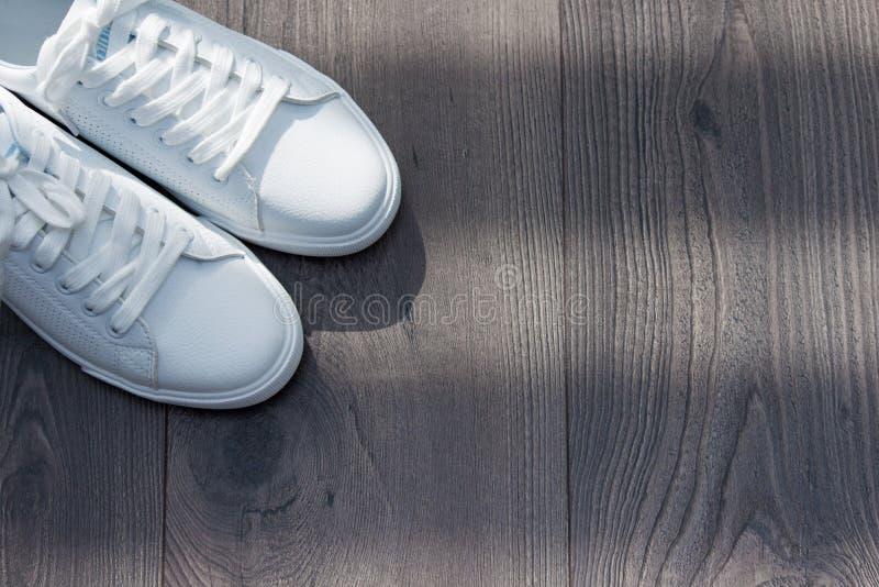 在鞋带的白色女性运动鞋鞋子在灰色棕色木背景 图库摄影