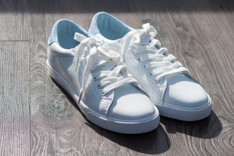 在鞋带的白色女性运动鞋鞋子在灰色棕色木背景 库存图片