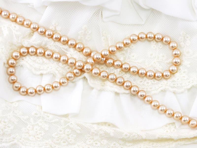 在鞋带背景的乳脂状的珍珠项链 库存图片