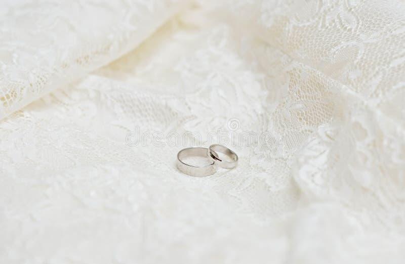 在鞋带背景的婚戒 库存图片