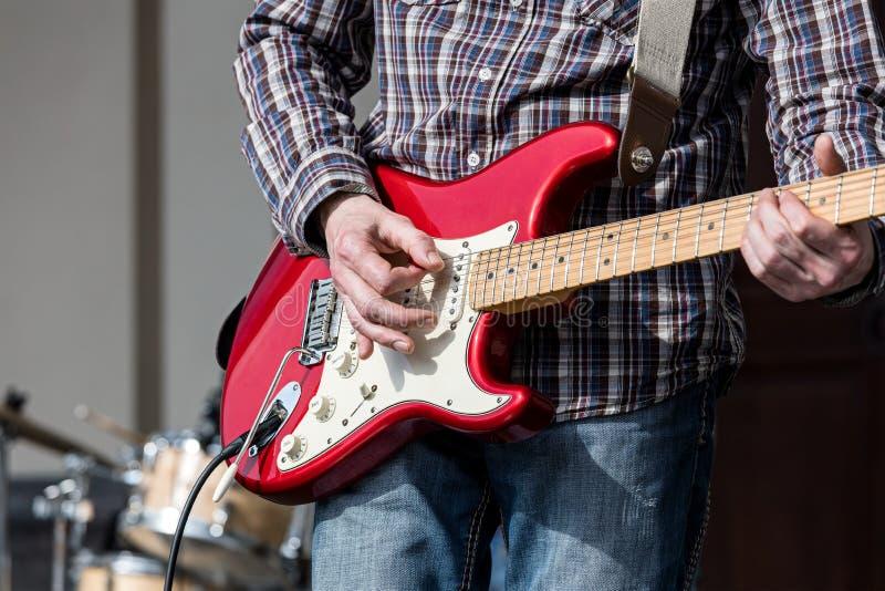 在音乐会期间,供以人员执行在电子吉他在街道 免版税库存图片
