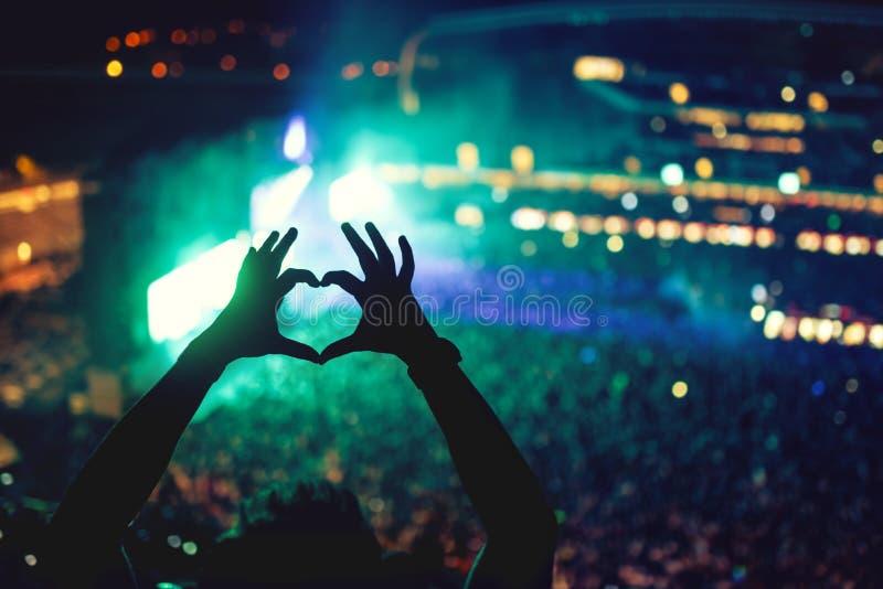 在音乐会的心形的手,爱艺术家和节日 与人享用的光和剪影的音乐音乐会 免版税图库摄影