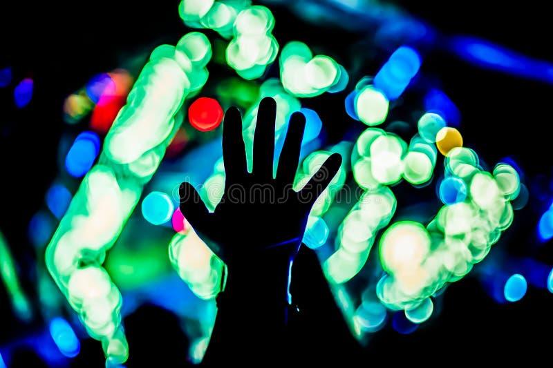 在音乐会节日的被举的手剪影和胳膊集会 免版税库存照片