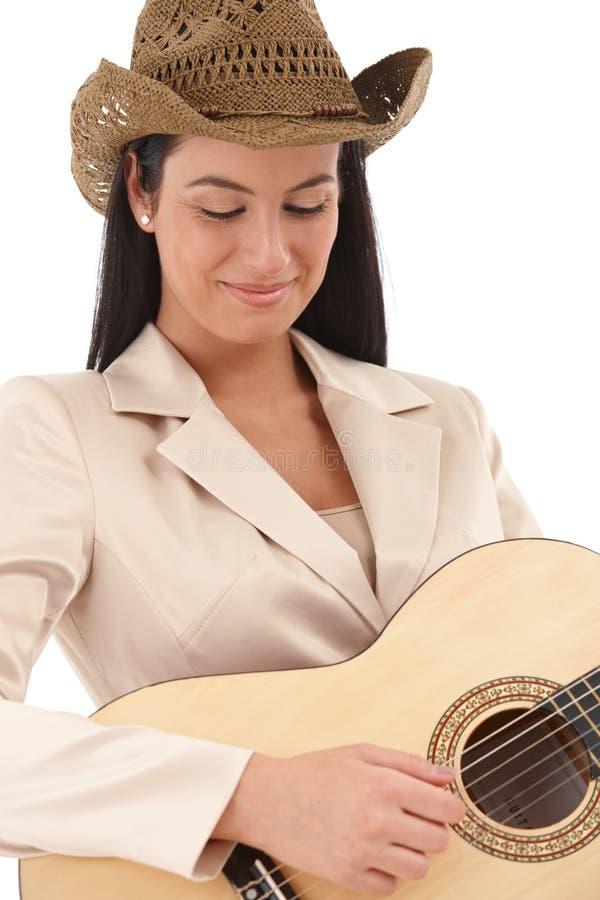 在音乐微笑失去的女性吉他演奏员 免版税图库摄影