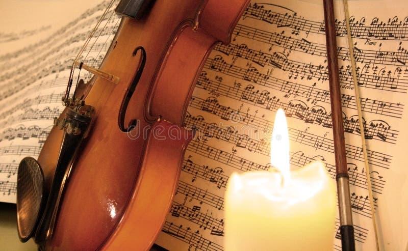 在音乐纸张的小提琴在一个蜡烛后 免版税库存图片