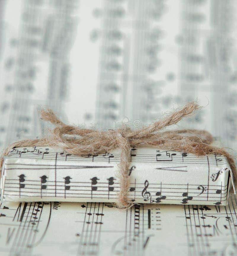 在音乐纸张的Giftbox 在笔记背景的一件音乐礼物 免版税库存图片