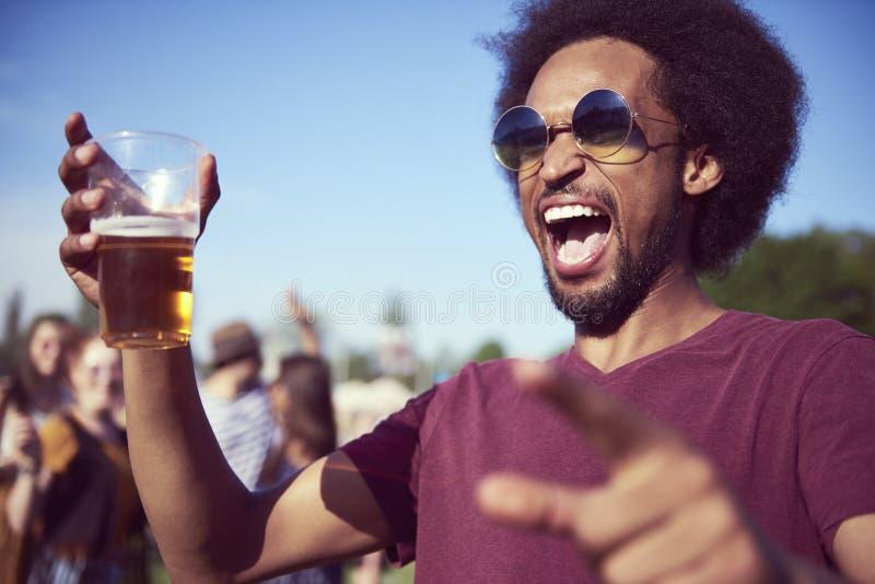 在音乐节的尖叫的非洲人饮用的啤酒 免版税图库摄影