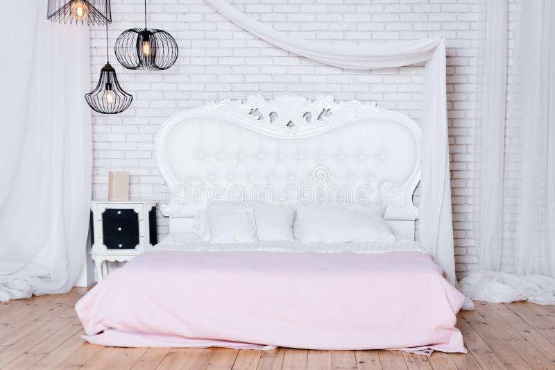 在顶楼公寓的加长型的床 顶楼有白色设计的样式卧室 免版税库存图片
