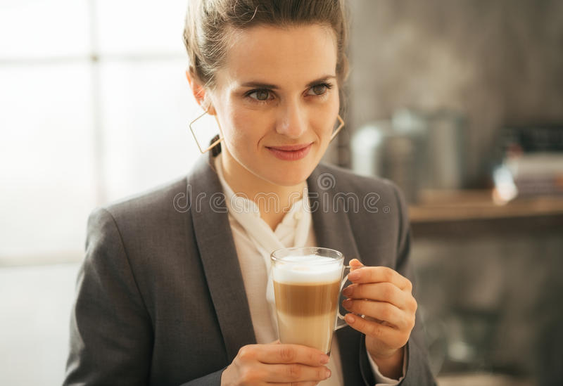 在顶楼公寓的女商人饮用的咖啡 免版税库存照片