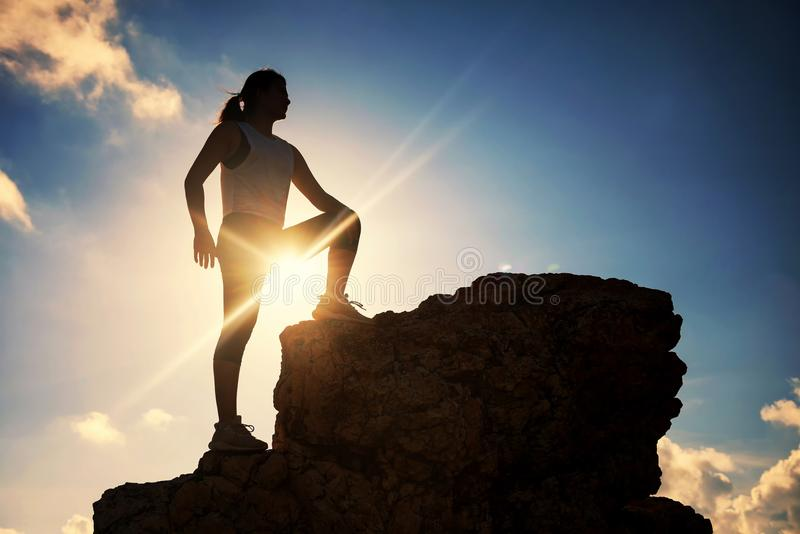在顶端剪影在日落的女性小山 图库摄影