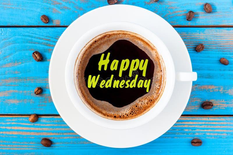 在顶视图咖啡杯的愉快的星期三在蓝色木背景用豆 库存照片
