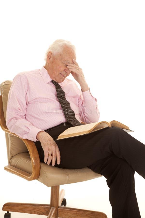 在顶头书的年长人桃红色衬衣手 免版税库存照片