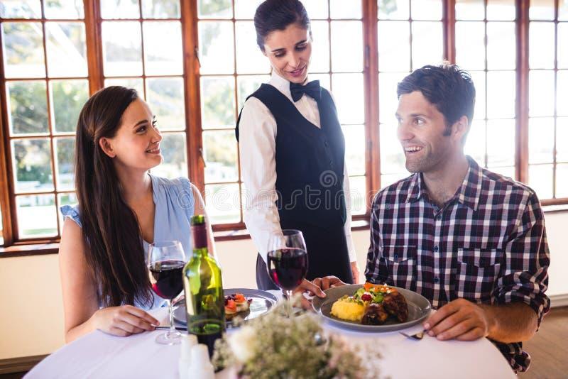 在顾客桌上的女服务员服务的食物板材 免版税库存图片
