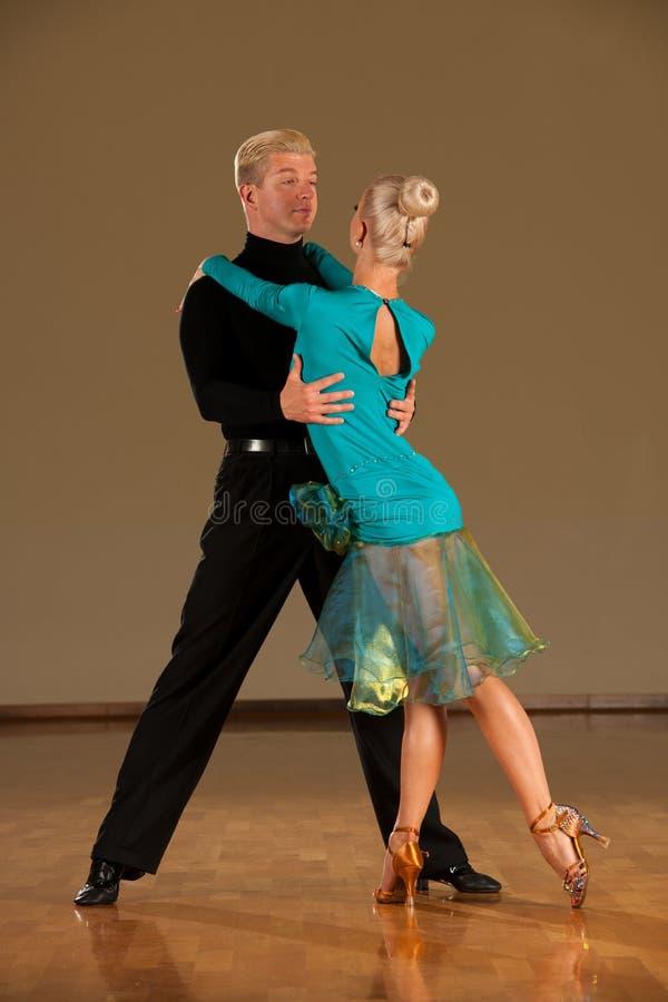 在预先形成陈列的行动的拉丁美州的舞蹈夫妇跳舞-狂放的桑巴 图库摄影