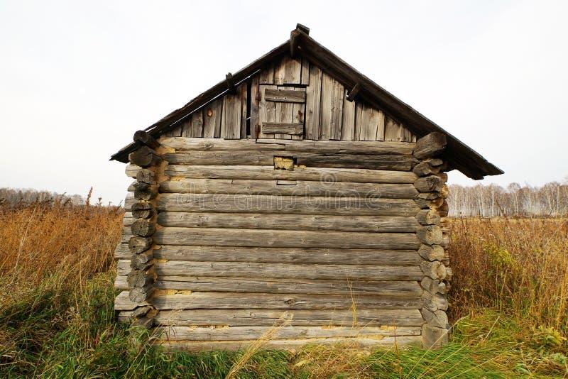 在领域中间的偏僻的老被毁坏的木房子 免版税库存图片
