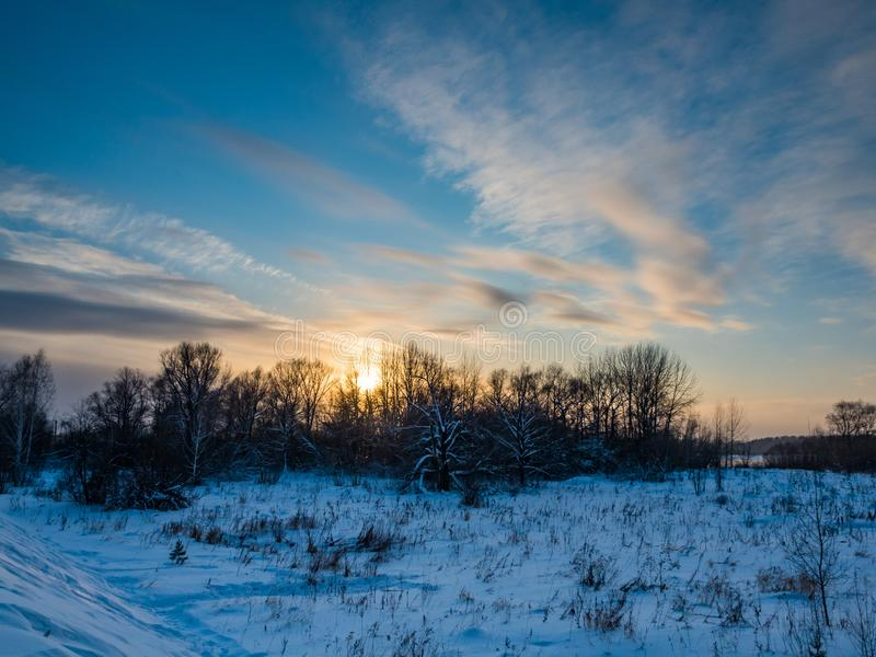 在领域和森林有云彩的,新西伯利亚,俄罗斯的冬天日落 库存图片