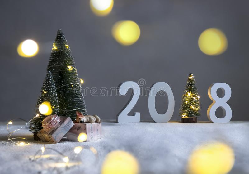 在领域在冷杉木下和在距离是图2018年在一棵圣诞树的角色与光的地方 免版税库存照片