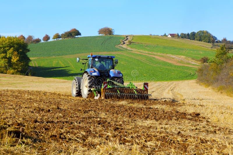 在领域工作的农用拖拉机 库存照片
