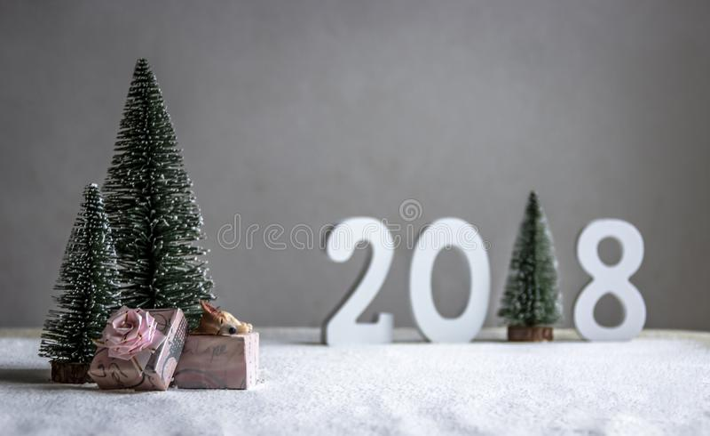 在领域狗在礼物睡觉,并且在距离图2018年在圣诞树的地方角色 库存照片