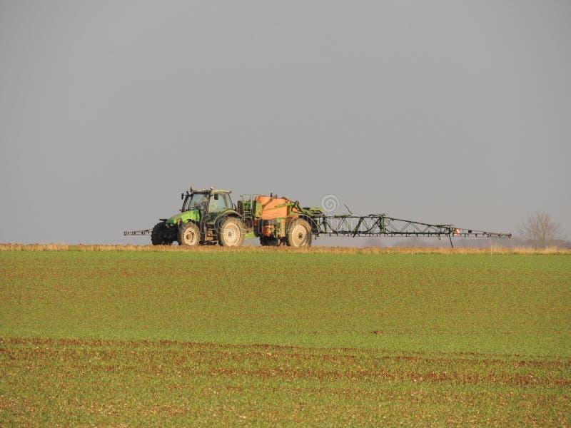 在领域的农夫喷洒的化学制品 免版税库存照片