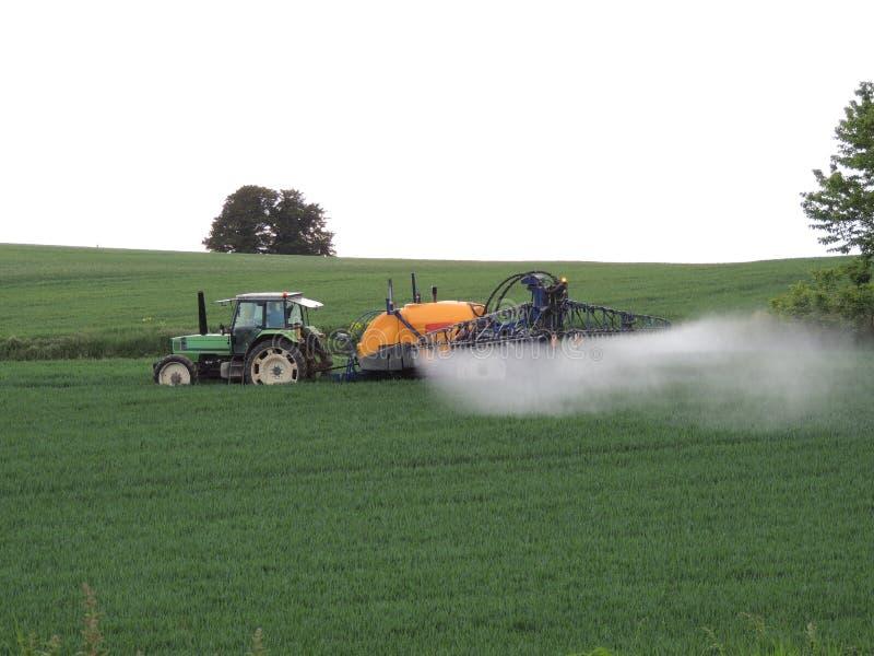 在领域的农夫喷洒的化学制品 库存图片
