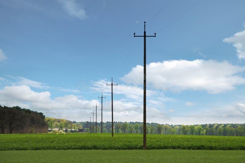 在领域的在backgrou的电源杆与绿色领域和云彩 库存照片
