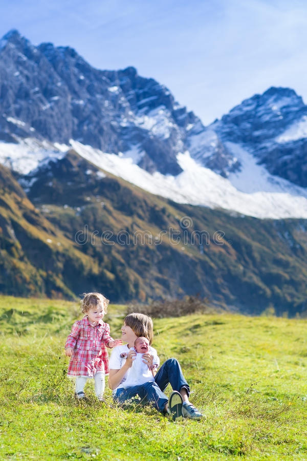 在领域的愉快的三个孩子在雪山之间 免版税库存照片