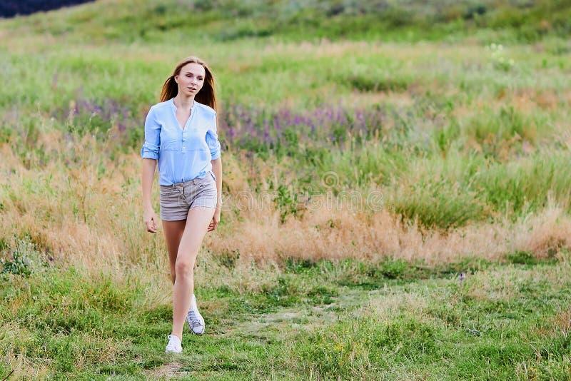 在领域的愉快的女孩佩带的蓝色牛仔裤夹克 免版税库存图片