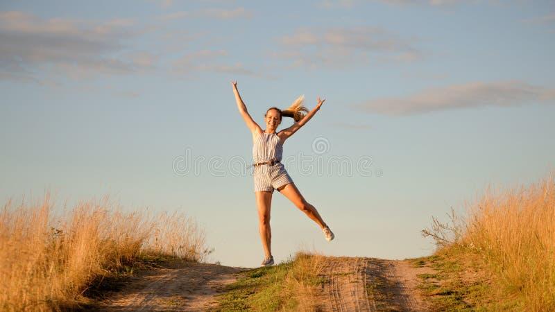 在领域的愉快的美好的女孩跳舞 免版税图库摄影
