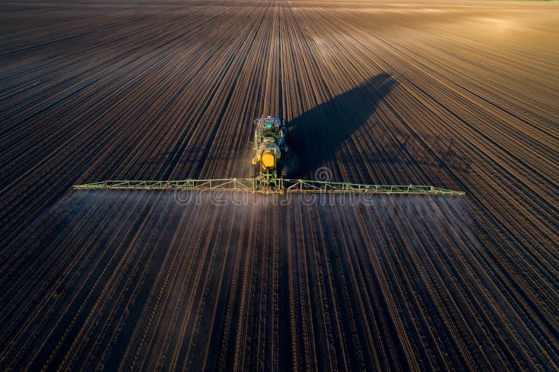 在领域的拖拉机喷洒的土壤 免版税库存图片
