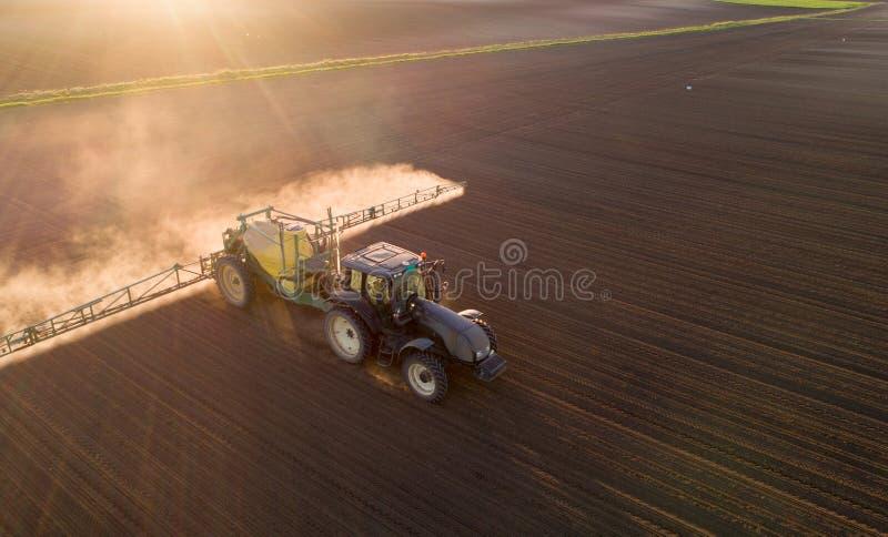 在领域的拖拉机喷洒的土壤 库存照片