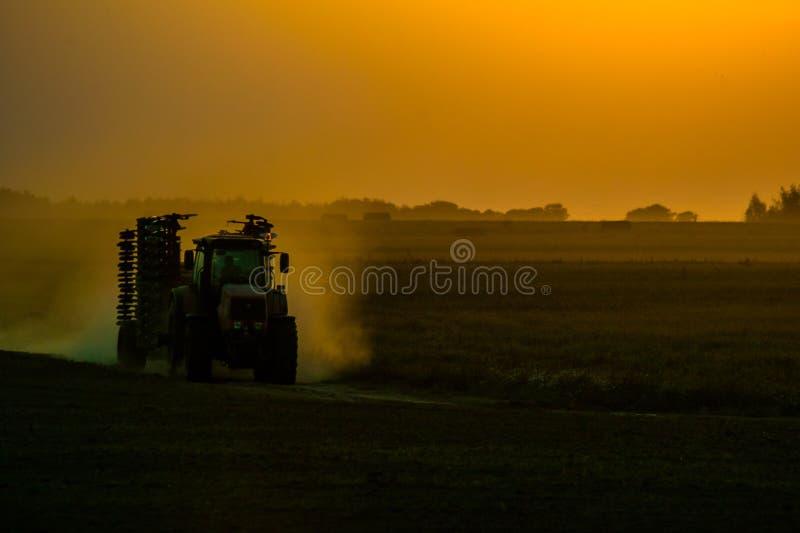 在领域的拖拉机在日落期间 免版税库存照片