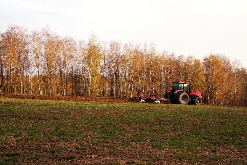 在领域的拖拉机在秋天犁地球 库存照片