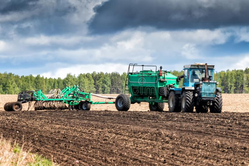 在领域的拖拉机工作播种的 免版税库存图片