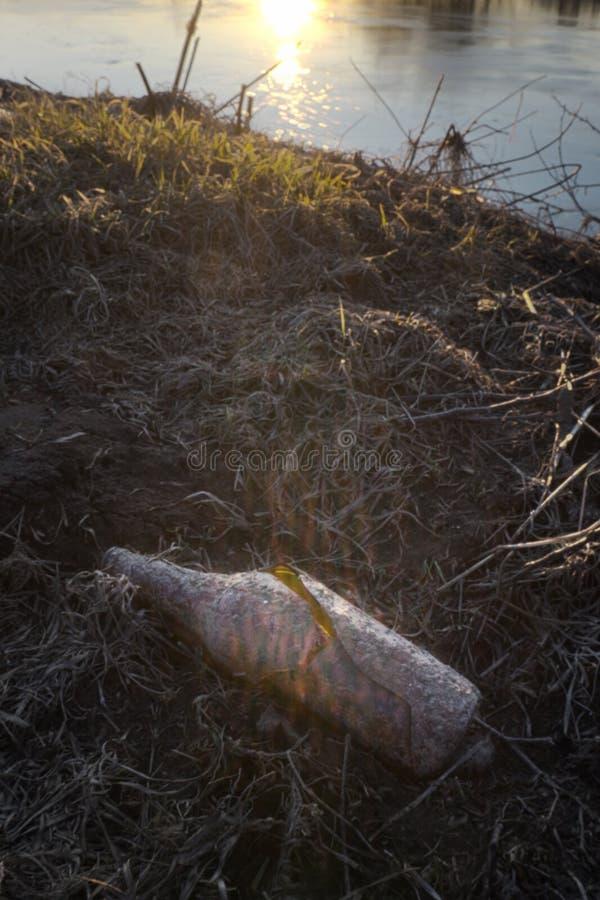 在领域的残破的玻璃空的瓶由落日的光 库存图片
