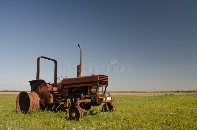 在领域的生锈的老被放弃的拖拉机 库存图片
