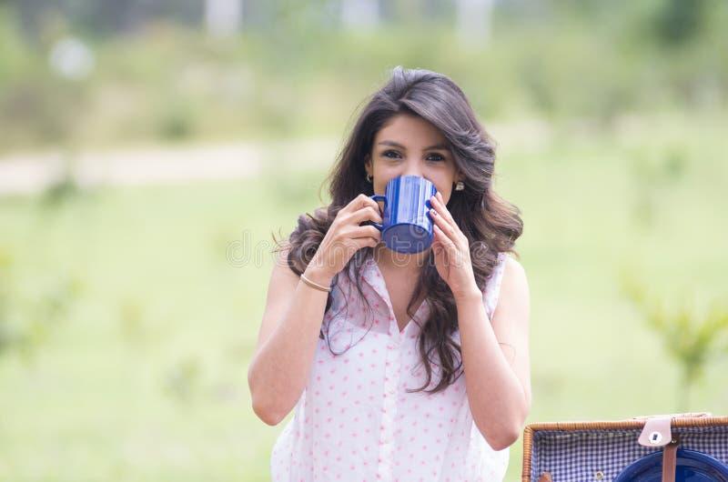 在领域的美丽的女孩饮用的咖啡 库存照片
