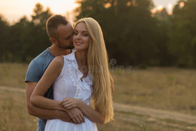在领域的美好的年轻夫妇在摩托车旁边 免版税图库摄影