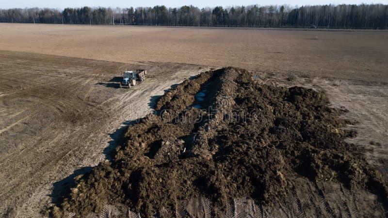 在领域的肥料堆 春天野外工作 ?? 免版税库存照片